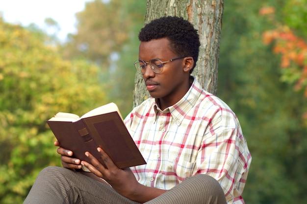 Il ritratto di un giovane uomo afroamericano intelligente e intelligente con gli occhiali e la camicia è shirt
