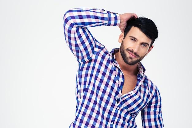 Ritratto di un bel macho guardando davanti isolato su un muro bianco