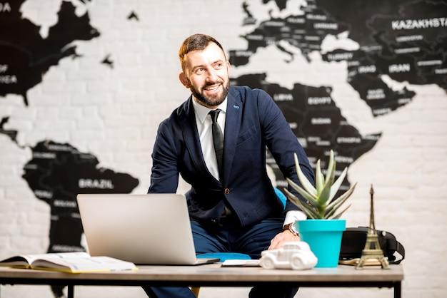 Ritratto di un bell'agente maschio che lavora con il computer portatile presso l'ufficio dell'agenzia di viaggi con una bella mappa sullo sfondo