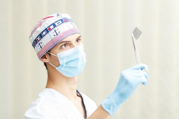 Ritratto del dentista maschio bello con i raggi x dentali in tenaglie dentali dell'acciaio inossidabile nella clinica odontoiatrica. medico che indossa uniforme bianca, berretto medico, maschera e guanti blu
