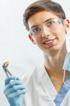 Ritratto di un bel dentista maschio con pinze o pinze dentali in acciaio inossidabile e dente inferiore estratto in esso. dottore in divisa bianca, occhiali e guanti blu