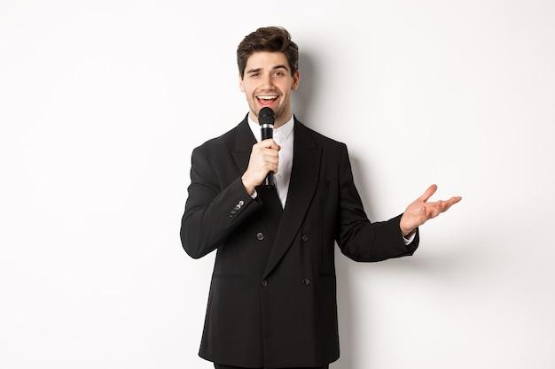 Ritratto di un bell'uomo in abito nero che canta una canzone, tiene in mano il microfono e fa un discorso, in piedi su sfondo bianco