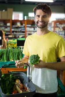 Ritratto dei broccoli d'acquisto dell'uomo bello e delle verdure differenti nella sezione organica