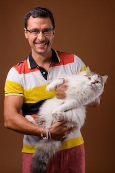 Ritratto dell'uomo bello che tiene gatto persiano su colore marrone