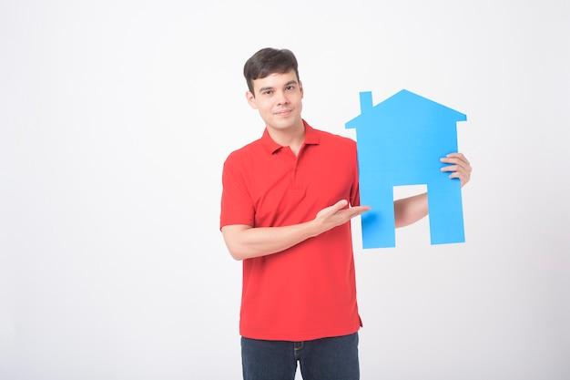 Il ritratto dell'uomo bello sta tenendo la casa di carta su fondo bianco