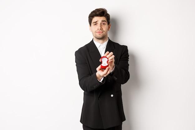 Ritratto di un bell'uomo che fa una proposta, chiedendo di sposarlo, mostrando l'anello, in piedi in abito nero su sfondo bianco.