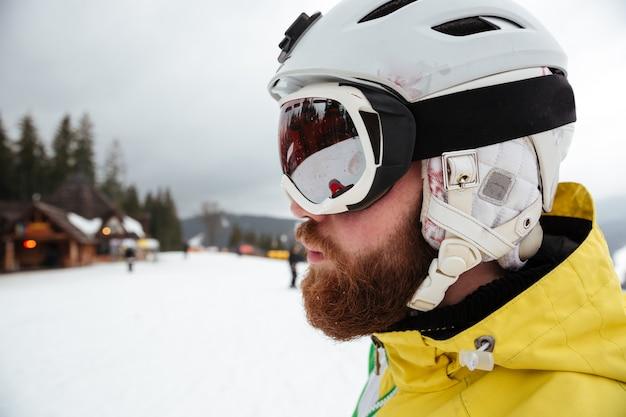 Ritratto di un bell'uomo snowboarder sulle piste gelida giornata invernale