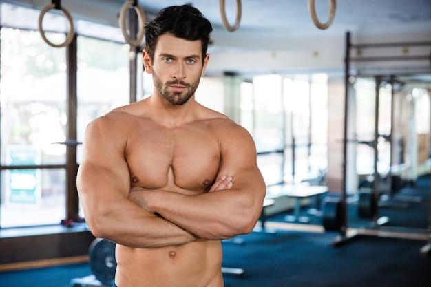 Ritratto di un bell'uomo in piedi con le braccia conserte in palestra