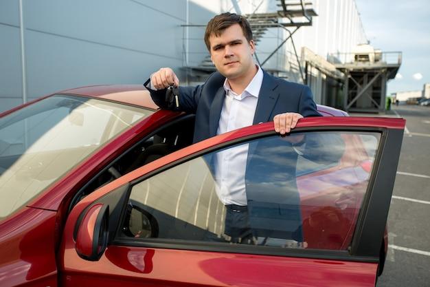 Ritratto di un bell'uomo in tuta appoggiato a un'auto nuova e che mostra le chiavi