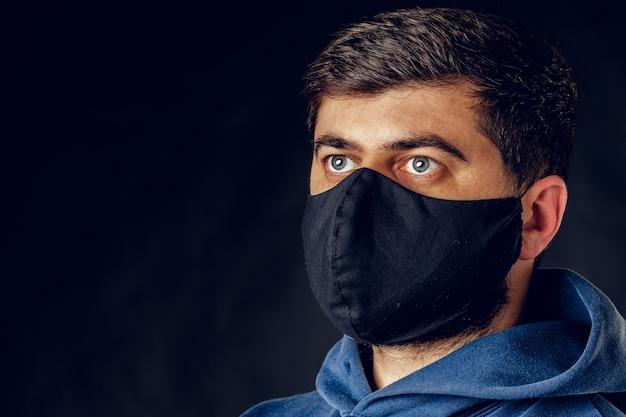 Ritratto di uomo bello che indossa maschera nera medica sul viso durante il blocco dell'epidemia di virus in posa sulla parete scura. avvicinamento.