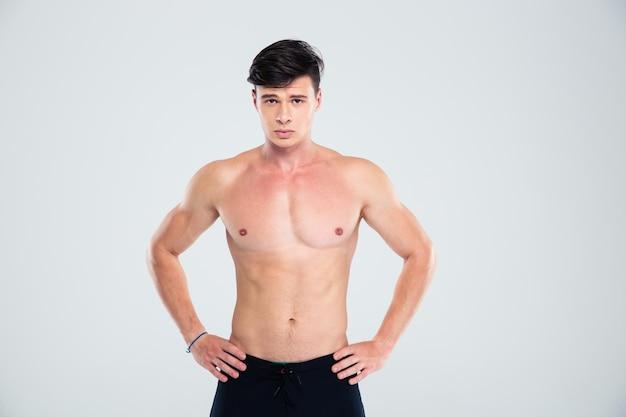 Ritratto di un bell'uomo con un corpo atletico in piedi isolato