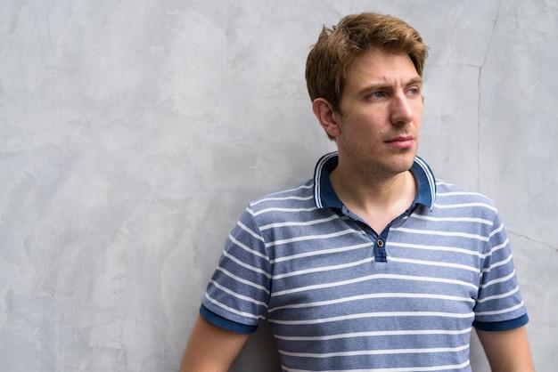 Ritratto di uomo bello con capelli biondi sul muro di cemento nelle strade all'aperto