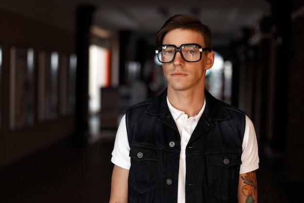 Ritratto di un bell'uomo con gli occhiali in vestiti di jeans