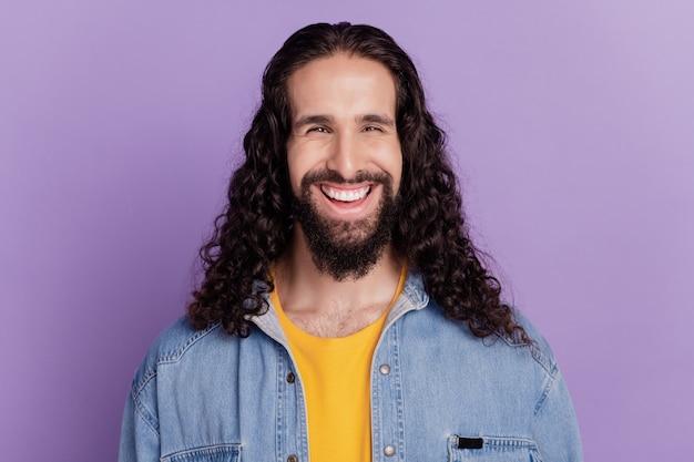 Ritratto di un bel ragazzo allegro mascolino che guarda la telecamera con un sorriso bianco splendente su sfondo viola