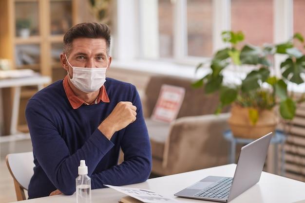 Ritratto di uomo maturo bello che indossa la maschera e guardando la fotocamera mentre è seduto alla scrivania in ufficio con una bottiglia di disinfettante in primo piano, spazio di copia