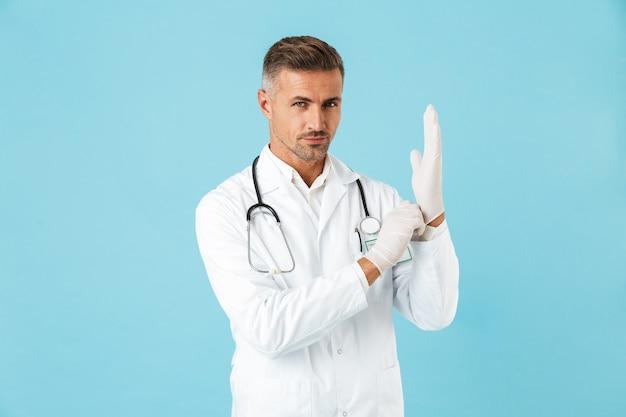 Ritratto di bel medico con lo stetoscopio che indossa guanti, in piedi isolato su muro blu
