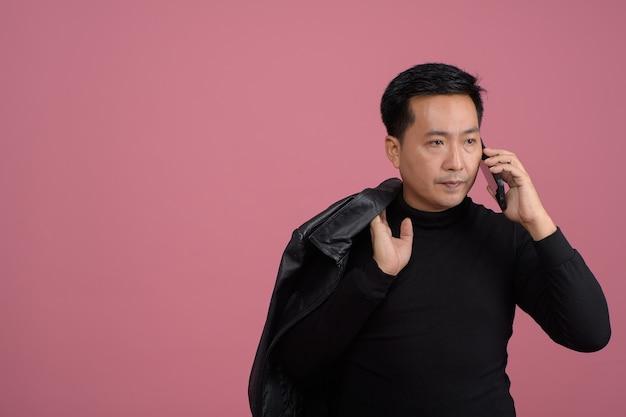 Ritratto di uomo asiatico di mezza età bello che indossa un maglione nero utilizza lo smartphone su sfondo rosa libero dallo spazio della copia.
