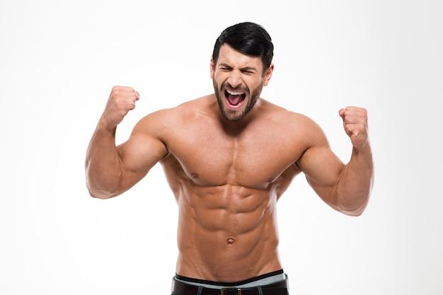 Ritratto di un uomo muscoloso bello che grida isolato su un muro bianco