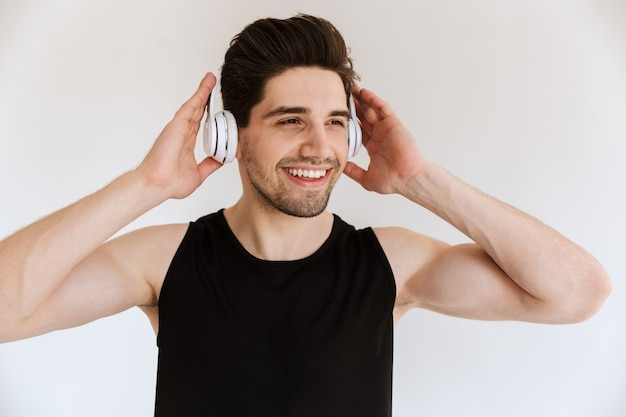 Ritratto di un uomo sportivo sorridente ottimista bello isolato sopra musica d'ascolto della parete bianca con le cuffie.