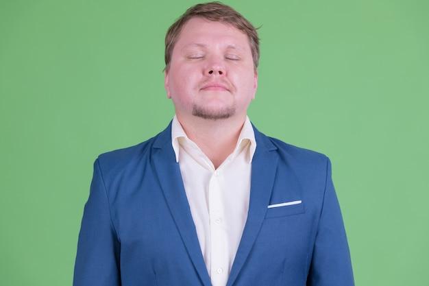 Ritratto di uomo d'affari barbuto in sovrappeso bello che indossa tuta contro la chiave di crominanza o la parete verde