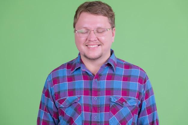 Ritratto di uomo bello hipster con la barba in sovrappeso con gli occhiali contro la chiave di crominanza o la parete verde