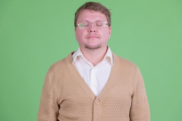 Ritratto di uomo barbuto in sovrappeso bello con occhiali da vista contro la chiave di crominanza o la parete verde