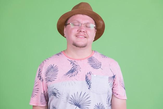Ritratto dell'uomo turistico barbuto in sovrappeso bello contro la chiave di crominanza o la parete verde