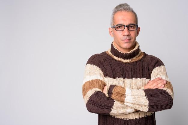 Ritratto di uomo persiano bello che indossa occhiali da vista con le braccia incrociate pronto per l'inverno