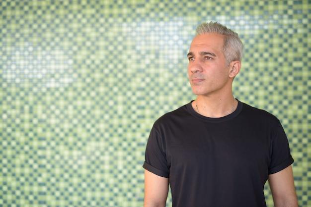 Ritratto di bell'uomo persiano con i capelli grigi contro la parete verde all'esterno