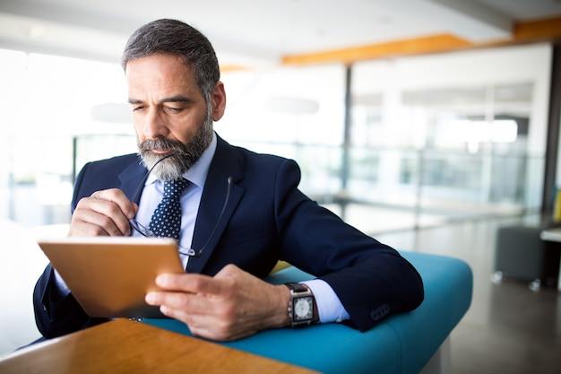 Ritratto di un bell'uomo d'affari anziano con tavoletta digitale nell'ufficio moderno