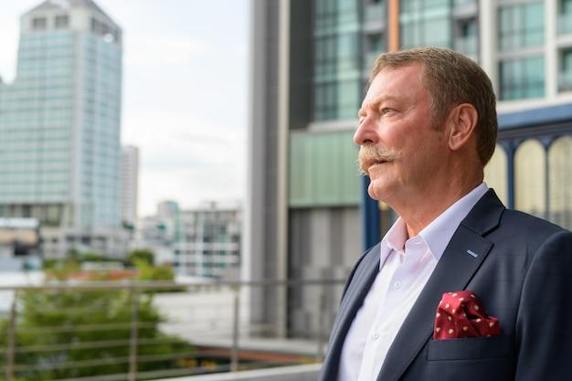 Ritratto di uomo d'affari senior bello con i baffi contro la vista della città