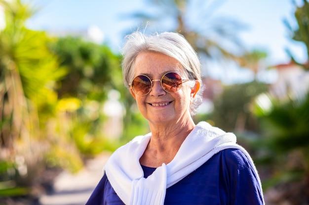 Ritratto di bella donna anziana all'aperto, guardando la telecamera sorridente
