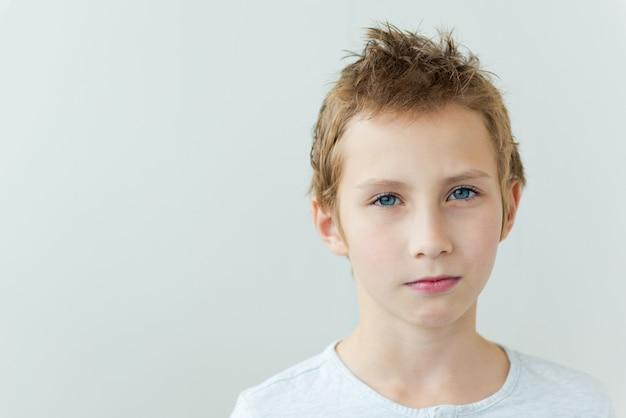 Ritratto di un bel ragazzo adolescente serio su sfondo grigio