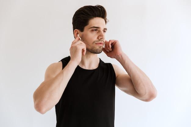 Ritratto di un giovane uomo sportivo serio bello isolato sopra la musica d'ascolto della parete bianca con gli auricolari.