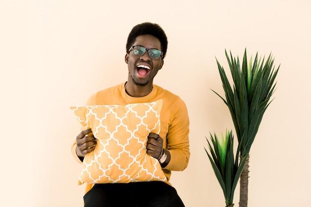 Ritratto dell'uomo afroamericano colpito bello che ride con il fronte sorpreso e felice. ragazzo africano in maglione giallo che tiene cuscino giallo, isolato su sfondo giallo chiaro