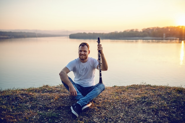 Ritratto dell'uomo biondo barbuto caucasico sorridente bello che si siede sulla scogliera e che tiene clarinetto.