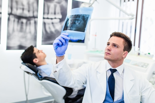 Ritratto di bel dentista sorridente guardando l'immagine a raggi x del suo paziente.