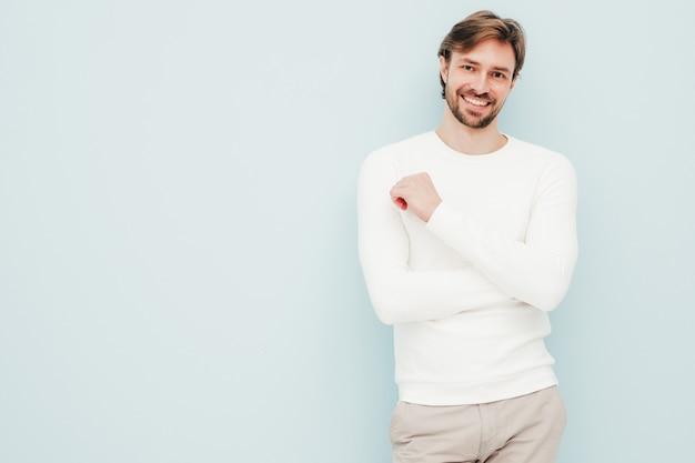 Ritratto di un bell'uomo d'affari lumbersexual hipster sorridente che indossa un maglione e pantaloni bianchi casual