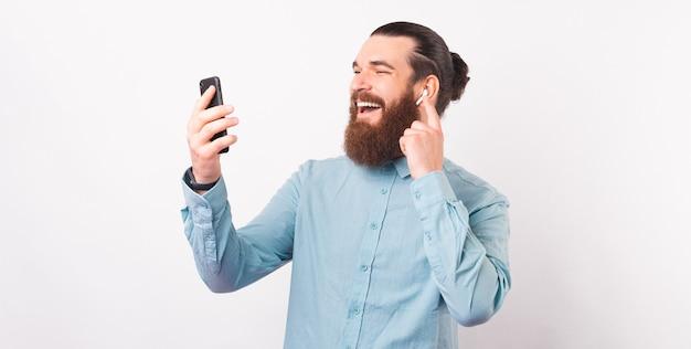 Ritratto di un bell'uomo sorridente che indossa una maglietta blu usando il telefono e gli auricolari