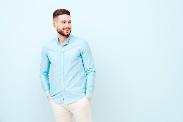 Ritratto di bel giovane sorridente che indossa camicia e pantaloni casual