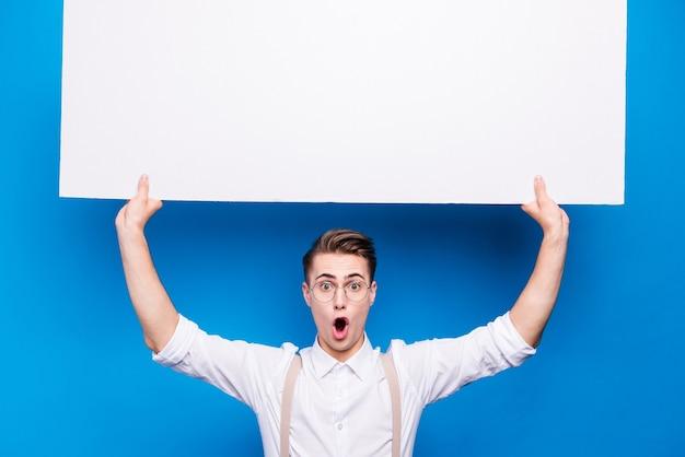 Ritratto di bello studente in posa contro il muro blu
