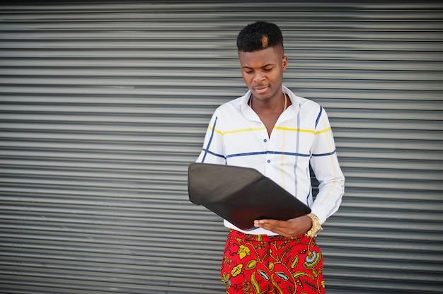 Ritratto di uomo di modello afroamericano alla moda bello in pantaloni rossi e camicia bianca con il computer portatile sulle mani contro il fondo d'acciaio dell'otturatore.