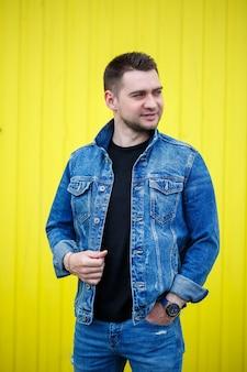Ritratto di un bel ragazzo elegante, un uomo vestito con una maglietta nera vuota in piedi su uno sfondo di muro giallo. stile urbano di vestiti, immagine alla moda moderna. moda maschile