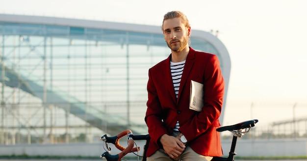 Ritratto di bel giovane alla moda in giacca rossa che guarda l'obbiettivo, tenendo il giornale sotto il braccio e seduto sulla bici. cavaliere di bicicletta casuale maschio che si appoggia e che posa all'aperto al moderno aeroporto di vetro.