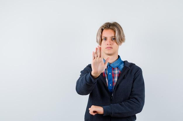 Ritratto di un bel ragazzo adolescente che mostra il gesto di arresto in camicia, felpa con cappuccio e sembra riluttante vista frontale