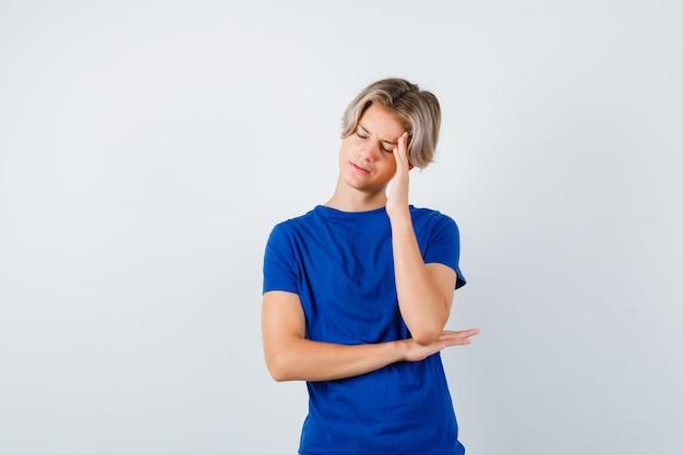 Ritratto di un bel ragazzo adolescente che soffre di un forte mal di testa con una maglietta blu e che sembra infastidito dalla vista frontale