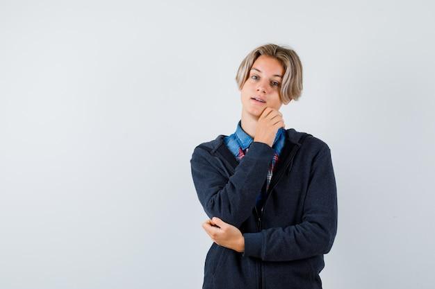 Ritratto di un bel ragazzo adolescente che si tocca il mento in camicia, felpa con cappuccio e guarda speranzoso in vista frontale