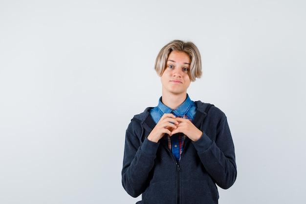 Ritratto di un bel ragazzo adolescente con le mani sul petto in camicia, felpa con cappuccio e vista frontale speranzosa