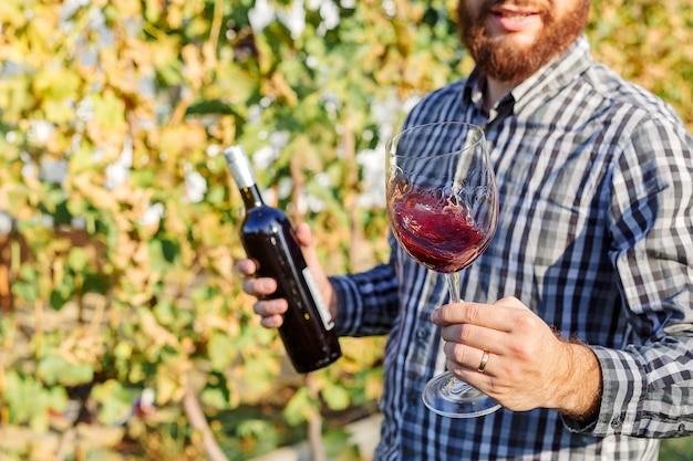 Ritratto di bel produttore di vino che tiene in mano una bottiglia e un bicchiere di vino rosso e assaggiandolo, controllando la qualità del vino nei vigneti