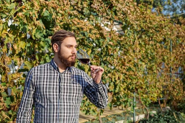 Ritratto di bel produttore di vino tenendo in mano un bicchiere di vino rosso e degustazione